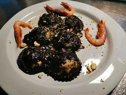 Ravioli al nero di seppia, zeste di limone, crostini di pane, granella di pistacchio e gambero rosso in crudo.