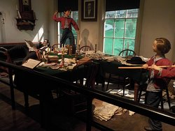 Exhibit  depicting two of Lincoln's sons playing in the father's law office while he calmly reads the newspaper.