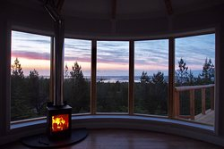 Looking out over the forest to the sunset sky and Vallay Island, from the comfort of your cabin and warming wood burning stove.