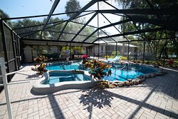 Tropical heated pool and spa in enclosed patio. Enjoy outdoor dining seating, BBQ and ping pong.