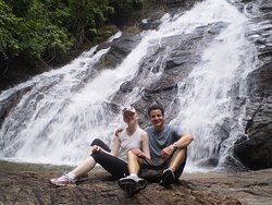 Cool down under a waterfall after completing the Turtles & Waterfalls bike tour.