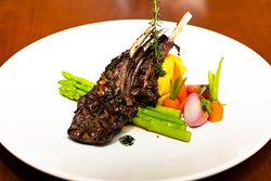 GRILLED RACK OF LAMB Grilled rack of lamb with mint sauce, served with roasted tomato, potato and chill