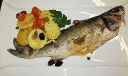 Branzino di giornata al forno con patate, capperi, olive tagiasche e pomodorini
