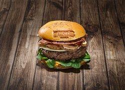 Cassius Burger 100% Ternera: Bacon crujiente, cheddar, tomate natural, mix de lechugas, aros de cebolla en tempura y salsa burger casera.