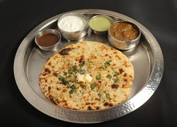 Stuffed Kulcha Served with Chhole/ Dal Makhani, curd and chutney.