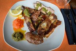Il nostro asado, cotto lentamente alla brace e accompagnato dalla salsa chimichurri e salsa criolla.