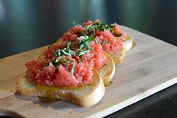 Bruschetta Homemade bread sliced and baked to a perfect crust and topped with fresh marinated cherry tomatoes and basil.