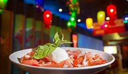 Prosciutto & Co Burrata cheese, sliced prosciutto crudo, marinated cherry tomatoes and fresh basil.