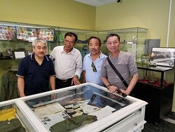 A helicopter veteran who landed on the USS Midway in Black April - the Fall of Saigon on April 30, 1975, stands with friends beside the original items he carried with him on that day and donated to the museum.