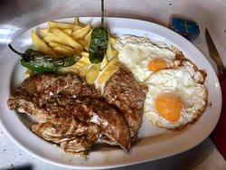 Plato combinado de filete de ternera, huevos y patatas.
