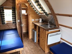 Inside a Wigwam - each Wigwam has a kettle, radiator, en-suite toilet, basin with hot & cold water), sink, fridge, double bed, singe bed and a three quarter bed that closes up into a bench seat.
