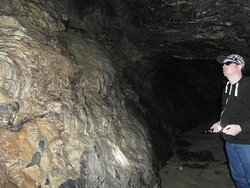 The limescale from the dripping water has covered the side of the cave