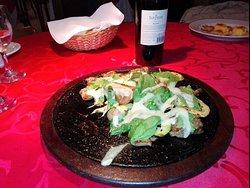 Lonjas de lomo con verduras grilladas, rúcula y parmesado en plancha caliente