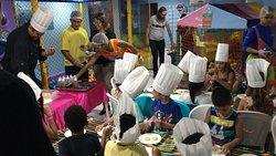 Chef da casa ensinando as crianças a fazerem Alfajor (dia das mães) no club kids do hotel.