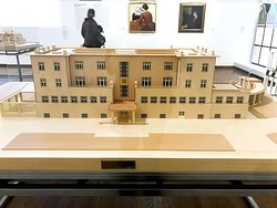 """A woman reads about artist Broncia Koller-Pinell in the background of the architectural scale model of Josef Hoffmann's Sanatorium Westend in Purkersdorf are Broncia Koller-Pinell's works: """"Young Woman Before Bird Cage: circa 1907"""" and """"The Pianist, undated"""" at the """"Vienna 1900: Birth of Modernism"""" permeant exhibit at the Leopold Museum in the MuseumsQuartier in Vienna, Austria. (Photo: Heather Cassell)"""
