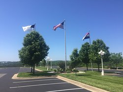 The grand flags located in the center of the front parking area.