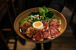 GYUNIKU RAMEN  makaron ramen w esencjonalnym bulionie z polędwicą wołową, pierożkami gyoza, groszkiem cukrowym, pak choi, jajkiem i grzybami shimeji ramen in aromatic broth with sirloin, gyoza dumplings, snap peas, pak choi, egg and shimeji mushrooms