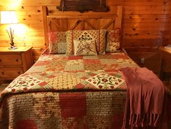 One of two comfy queen beds in Miss Kitty's Rendezvous cabin