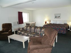 King Suite includes a King Bed, a dining table, extra sofa bed and 2 recliners. As well as a microwave, coffee pot, refrigerator
