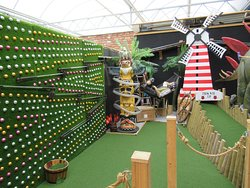 Here, the ball goes under the windmill, then travels up, goes along to the left and then either comes out around the totem pole or travels along the left wall which is covered in golf balls as well!