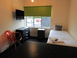 First part of room containing kitchenette and single bed, chest and TV