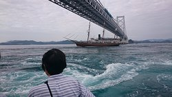 目前の大渦と海峡を跨ぐ大鳴門橋、その下を運航中の帆船咸臨丸!Goodタイミングのお客様ですね!うずしお汽船後部デッキより望む。