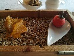 """Ancora il """"benvenuto"""" dalla cucina: sulla destra un finto pomodoro (fatto di burro di cacao) con pomodoro e burrata all'interno che esplodono in bocca"""
