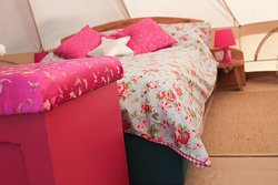 The Starry Night bell tent is what glamping is all about. It's a beautiful, light & spacious tent, with comfy beds, cosy duvets, fairy lights and a deck to sit out and look up at the starry sky - perhaps with a glass of something cool & refreshing in your hand.  *Sleeps 4 (1 double bed & 2 singles) *Perfect for a couple, or a family of 4. *All bed linen provided. *2 electric lamps & fairy lights inside. * 2 spare sockets to charge phone. *Close to bathrooms. *Small private deck area.