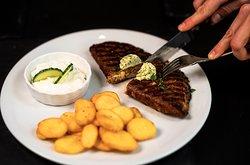 Bifteki aus dem Grill, gefüllt mit Schafskäse, dazu Tzatziki, frittierte Kartoffelscheiben und Salat