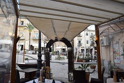 The beautiful nice little entrance of the terrasse! Cover terrasse, perfect to enjoy the view and the vibe of the square even on a rainy day!