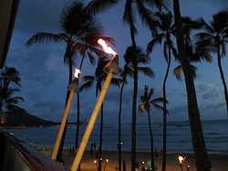 Flaming torches light up the darkening sky with view of Diamond Head and Waikiki Beach from balcony of Hula Grill