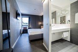 Double bedroom witg open and spacious bathroom in clean Scandinavian design
