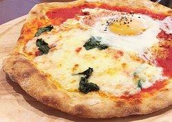 """ピッツァ「ピアチェーレ」。ピッツァの王道「マルゲリータ」と、マルゲリータをベースにピリ辛に仕上げた「ピッカンテ」をハーフ&ハーフにし、さらに洞爺湖畔で育った""""三四郎卵""""をトッピングした欲張りな味わい。"""