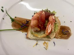 Artisan bread topped with crawfish wrapped into speck layered on a potato edge and Summer greens.
