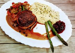 Reindeer medallion with bacon, sautéed vegetables, asparagues, sauce and mashed potatoes