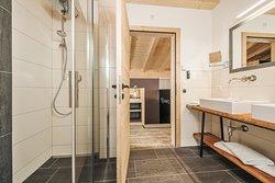 Offenes und großzügiges Badezimmer mit begehbarer Dusche. Gestellt werden Hand- und Badetüchern, sowie Föhn und Radio sind vorhanden.