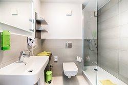Das modern eingerichtete Bad verfügt über Dusche, WC, Fön sowie Handtuchheizung. Diese Zimmerkategorie ist allergikerfreundlich.