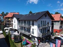Widok od strony ulicy Korczka, widać tam sklep oraz plac zabaw dla dzieci