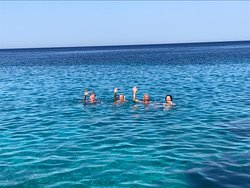 4happy holiday makers waving on their private swim in a cove