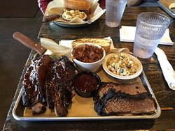 My 3 meat plate, 2 beef ribs, 2 slices beef brisket and pulled pork  in the small bowl at the center with side of macaroni salad and Texas toast. The plate at the top is my grandsons pulled pork sandwich and potatoe salad.