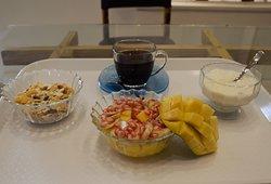 Healthy breakfast: müesli with curd/milk, honey, fruit salad and tea/coffee