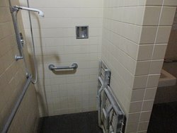 ADA shower stall with hand held shower faucet locked in position so it sprays water on your feet not your body m