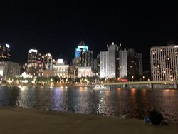 The View of the city at night time off of the boat.