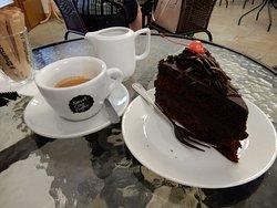 Fetta di torta al cioccolato e caffè americano al tavolo