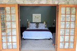 Milkwood Trail Cottage (sleeps 4 adults, 2 kids). Master bedroom with doors opening onto a veran