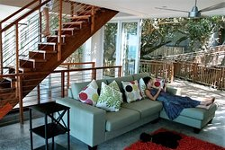 Glass sliding doors open from the living area to the sheltered forest and to the ocean