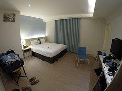 a single sofa, a small table, a desk, a chair, a tv, bed, safety box, closet
