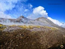 Escursione in visita ai Crateri attivi del vulcano Etna, i primo piano il Cratere di Nord Est e le esalazioni gassose