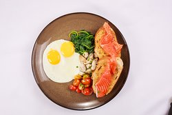 Fried Eggs or Omelette with smoked salmon, warm spinach  mushrooms and tomatoes on multigrain bread