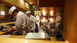 Tre sushi shokunin e due assistenti oltre due cameriere al lavoro per 10 clienti al primo piano